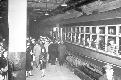 Crowds board commuter trains at City Hall station during WWII (circa 1944)