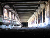 The light spilling into the Aqueduct through it's arches reveals a debris covered floor, graffiti, and steam pipes.