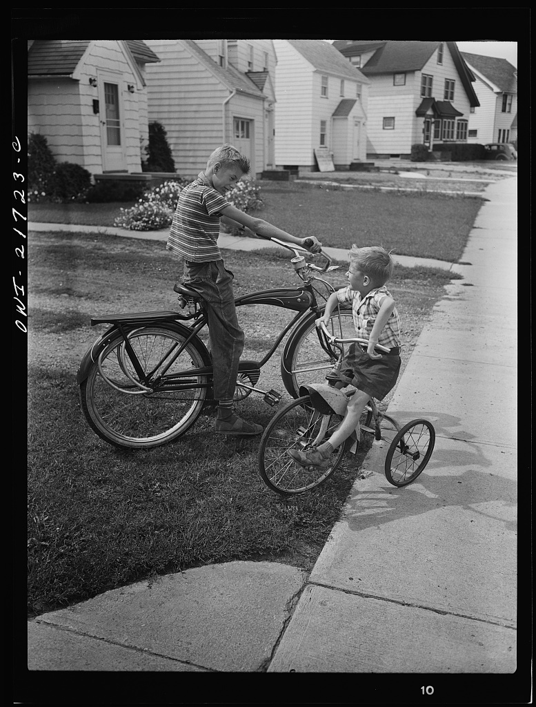 Howard and Earl Babcock playing in front of their house with their cycles [PHOTO: Library of Congress]