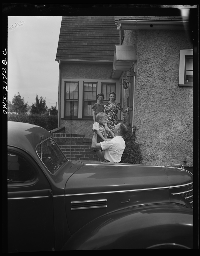 Mrs. Babcock, Shirley, and Earl greeting Mr. Babcock in front of the house [PHOTO: Library of Congress]