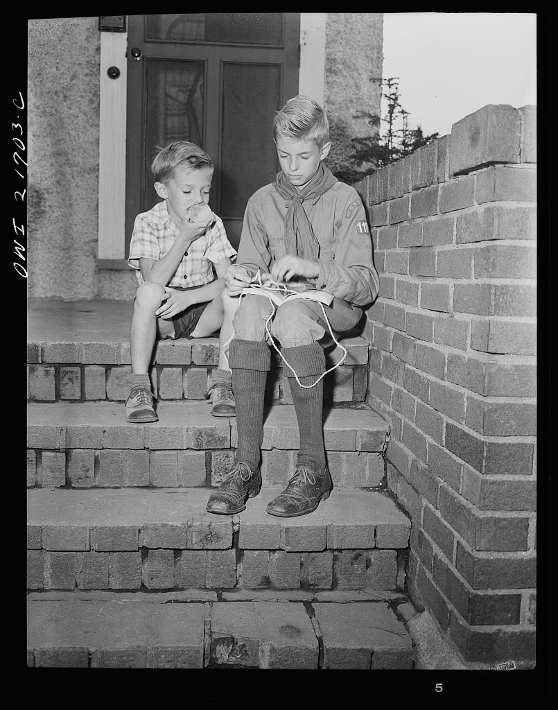 Earl Babcock watching while Howard, his brother, in his Boy Scout uniform, practices tying knots [PHOTO: Library of Congress]