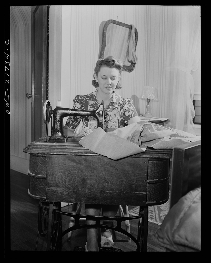 Shirley Babcock is very handy at the sewing machine and she helps her mother with the family sewing [PHOTO: Library of Congress]