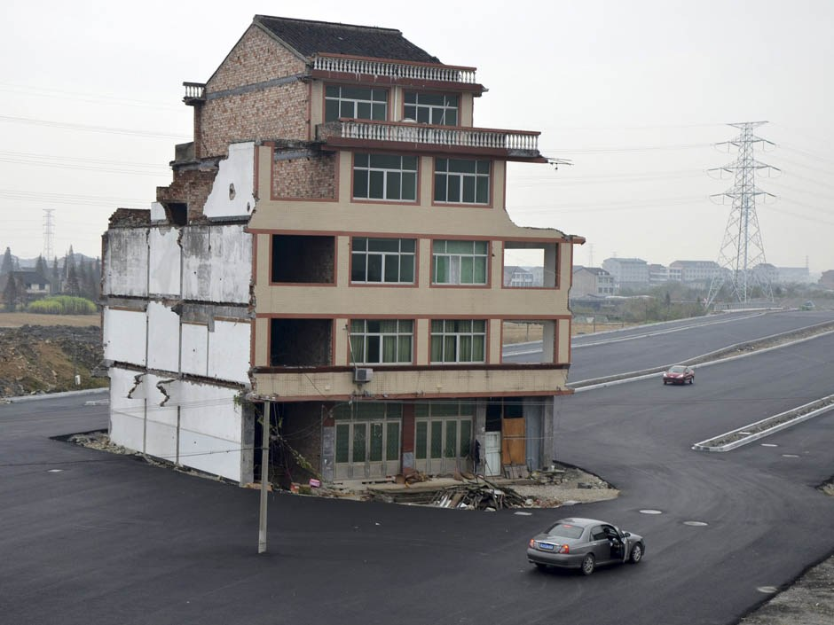 A car stops beside a house in the middle of a newly built road in Wenling, Zhejiang province, November 22, 2012. [PHOTO: REUTERS/China Daily]