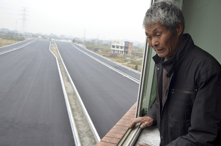 Mr. Luo looks down from his house which stands alone in the middle of a newly built road in Wenling, Zhejiang province, November 22, 2012. [PHOTO: REUTERS/China Daily]