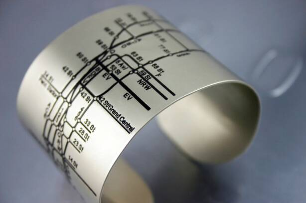 Accessorize with the NYC Metro Cuff—a matte metal bracelet embossed with the subway lines, numbers and streets of Manhattan.
