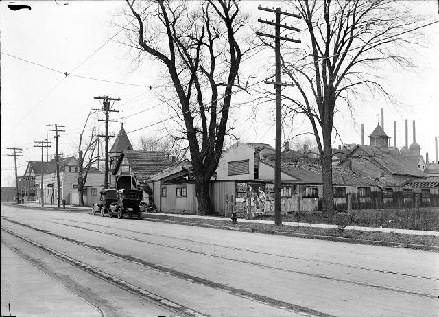 A view of Beach Avenue west of Lake Avenue. Buildings to be torn down for an automobile parking space are pictured as well as Manitou Trolley tracks in the foreground and the Charlotte blast furnace and chimney in the background. [PHOTO: Albert R. Stone]