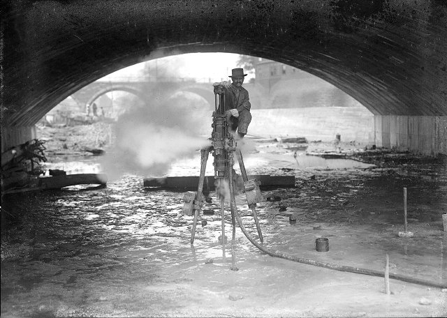 Here a workman poses with his steam drill under the Broad Street Bridge. Explosives will be used to deepen the river bed. [PHOTO: Albert R. Stone]