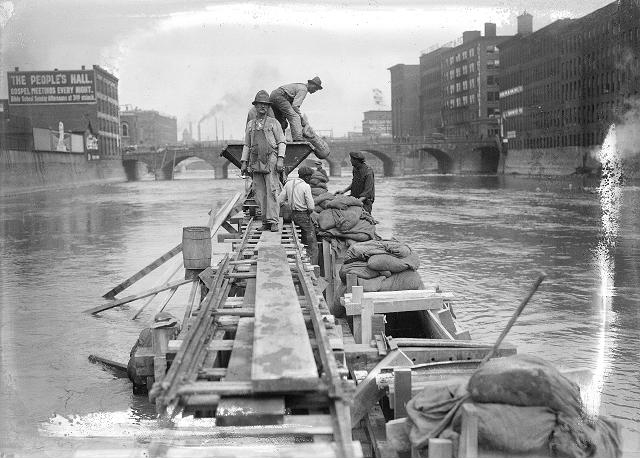 Men work from narrow wooden platforms filling concrete forms with sand bags. [PHOTO: Albert R. Stone]