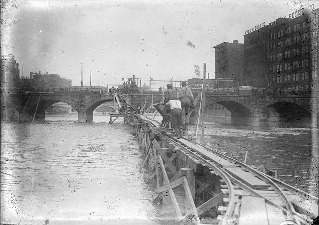 Three workmen push a hopper along a raised trestle in the middle of the Genesee River. [PHOTO: Albert R. Stone]
