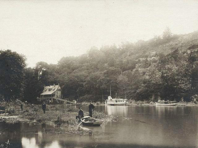 The Glen House, seen from river level, looking west. The scene shows a paddle wheel steam boat, the City of Rochester. A rowboat and men are along the bank of the river. [PHOTO: Rochester Public Library]