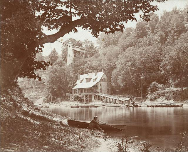 A view of the Glen House and its elevator along the banks of the Genesee River. In the foreground is a man in a straw hat seated by a rowboat.  [PHOTO: Rochester Public Library]