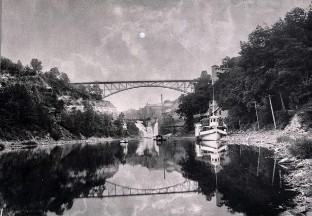 A view of the Genesee River, looking south towards Driving Park Avenue Bridge and the Lower Falls. A large boat is docked at the Glen House on the right.  [PHOTO: Rochester Public Library]