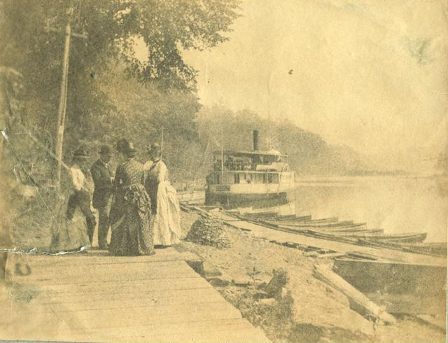 Passengers wait to board the City of Rochester steamboat at the Glen House resort boat landing. Looking down lower falls. The steamer leaves here for the mouth of river and Lake Ontario about 5 miles north. Sometimes it travels as far as Seabreeze. c.1886-1889. [PHOTO: Rochester Public Library]