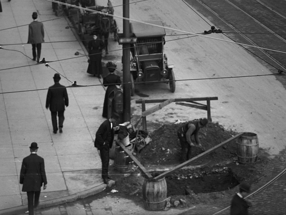 A close up view of a worker filling in a giant pothole on Main Street. Rochester, NY. c.1908. [PHOTO: Detroit Publishing Co. via Library of Congress]