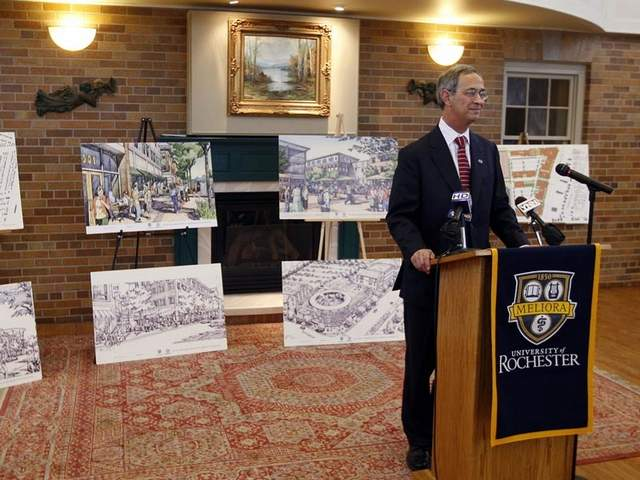University of Rochester president Joel Seligman showing off plans for College Town. Original plans included an enclosed public transit center. The latest plans include twice as much parking as originally called for and no transit center. [PHOTO: Democrat & Chronicle]