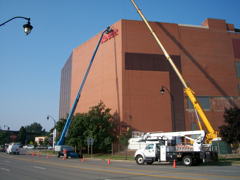 What are workers doing with the sign Kodak at the former Kodak Park?