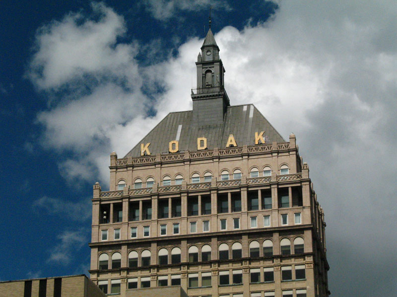 Kodak Tower TODAY: as it stands today with bad windows that don't fit the openings, dirty patched up roof, dinged up sign, and a cupola that is painted gray for some reason.