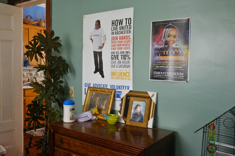 This poster in Mary's living room recognizes her community volunteer efforts. Next to Mary's poster is another in memory of her grandaughter Shawntayvia Williams. [PHOTO: Julie Gelfand]