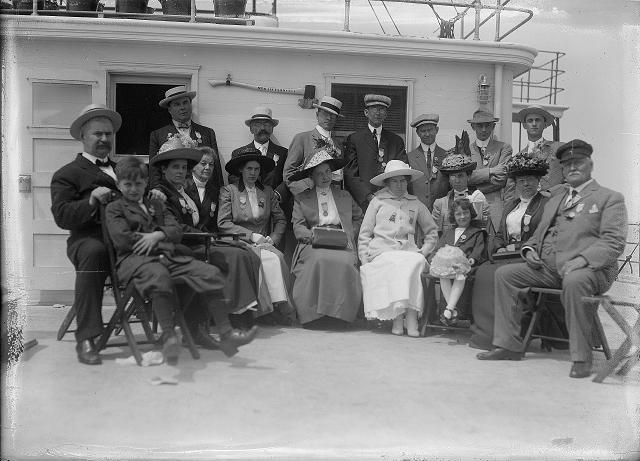 Crowd of people, including a band, in the bow of the car ferry Ontario I, as the boat leaves Charlotte. The group is the Rochester Common Council on an outing in Coburg. July 26, 1912. [PHOTO: Albert R. Stone]