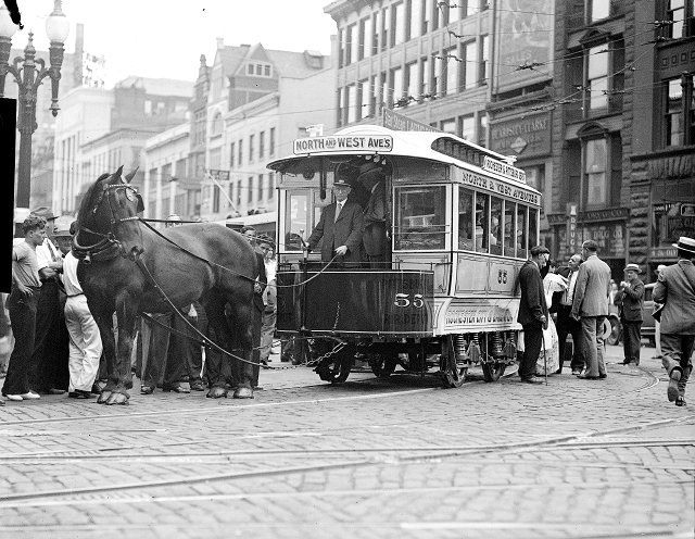 A horse-drawn streetcar rounds a corner near Main Street. It is car number 55 of the Rochester City & Brighton Railroad Company. The car was later added to the collection at the Transportation Museum in Henrietta. In this photograph many people are gathered around to examine the streetcar. This may have been a parade to celebrate the Rochester Centennial in 1934. [PHOTO: Albert R. Stone Collection]