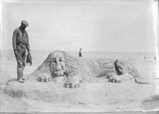 Robert Pernell stands next to a life-sized lion he has sculpted from sand in Charlotte. Printed in Rochester Herald, August 6, 1922.