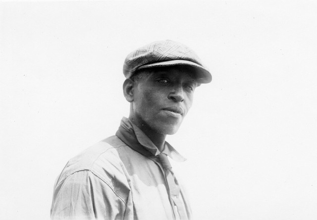 This is a close up of Robert Pernell, an African-American sand artist. He has been entertaining crowds at Charlotte Beach with his huge sand sculptures. Printed in Rochester Herald, August 6, 1922.
