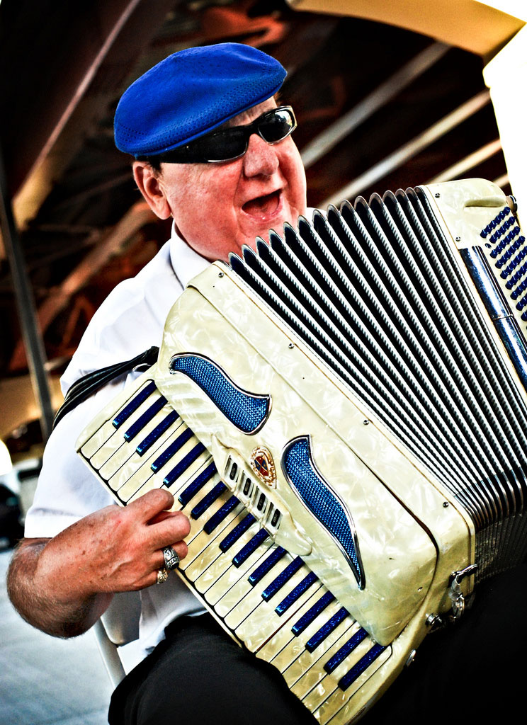 Walter, Rochester's accordion man, performing underneath the Freddie-Sue bridge in Corn Hill as a crowd gathers for the Eddie Money 'Party in the Park' concert [PHOTO: Jeff Gerew, C7Photo.com]