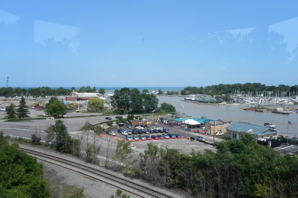 A view from atop the lighthouse, looking down on the area that was once marsh and sandbars. In the distance and slightly to the left, you can see Ontario Beach Park; the large white building in front of the line of trees is the Port of Rochester terminal. [PHOTO: Joanne Brokaw]