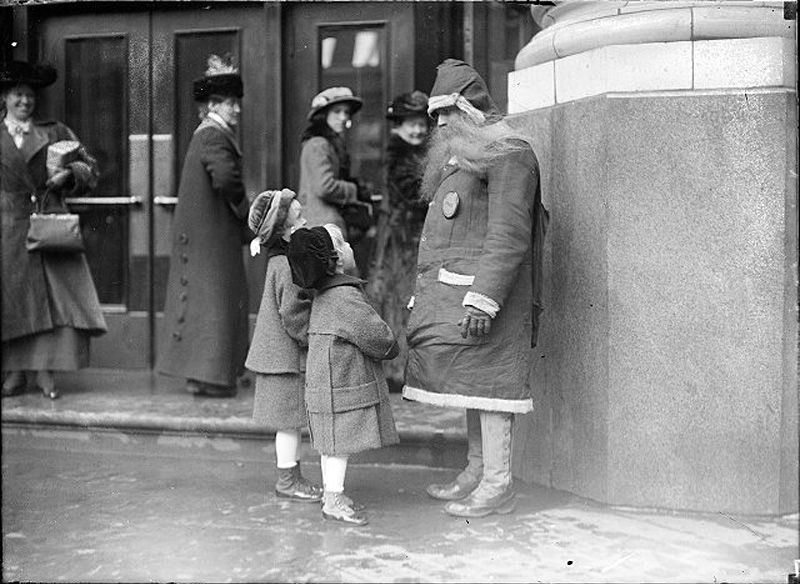 Two little girls have a chat with Santa in front of the Duffy-Powers Department Store on the corner of W. Main and Fitzhugh Streets, Rochester, NY. Printed in Rochester Herald, December 24, 1914. [PHOTO: Albert R. Stone collection]