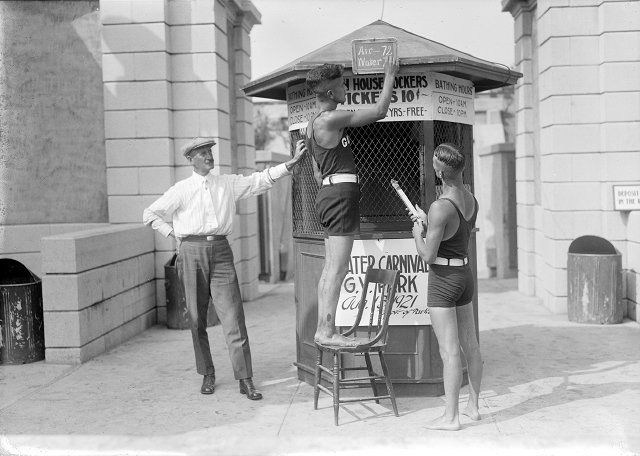 Frank Warren, ticket agent at the Durand-Eastman Park bathhouse, watches the lifeguards at work. Bud Martin and Roy Ackerman are writing the water and air temperatures on the chalkboard. August, 1921. [PHOTO: Albert R. Stone]