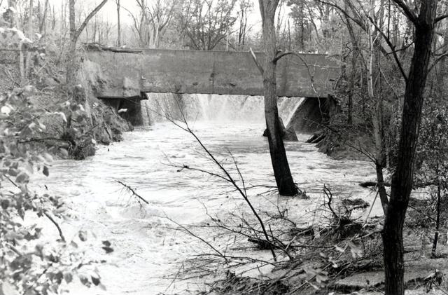 This view shows the water pouring out of the canal from below. A wall of water about two stories high ripped through residential streets damaging 69 homes. [PHOTO: Perinton Municipal Historian collection]