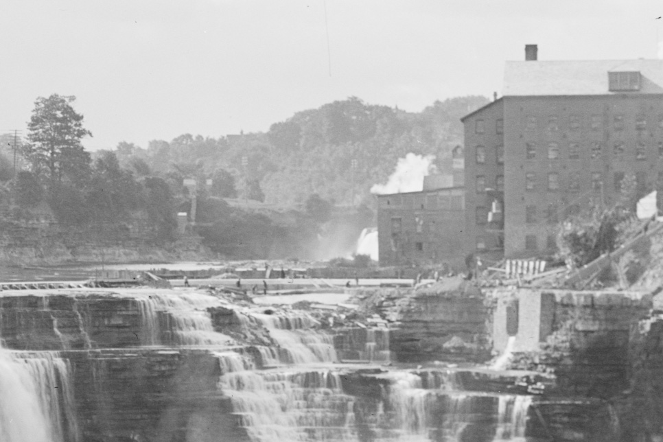This was a busy busy time in Rochester. These workers on the rim of Lower Falls are constructing a dam, several feet high to regulate the flow for the electric generators.