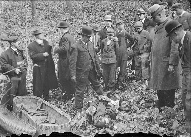 Detectives, men from the coroner's office, and bystanders gather around Francesco Manzello's dismembered body. It was found in a gully in Webster, packed into a whiskey barrel. The parts of the body had been folded up to fit into the barrel: his arms clasp his legs, which have been reversed, and his head rests on his arms and feet.  [PHOTO: Albert R. Stone]