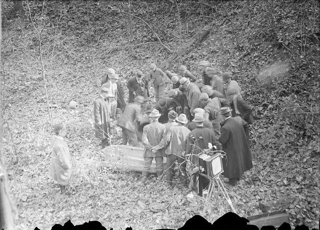 Detectives, men from the coroner's office, and bystanders gather around Francesco Manzello's dismembered body. [PHOTO: Albert R. Stone]