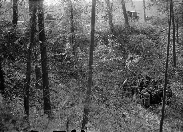 This distance shot shows the group of men gathered in the bottom of the gully. Along the top of the image can be seen the guard rails along the Webster State Road, men standing behind the rails, and vehicles parked along the road. [PHOTO: Albert R. Stone]