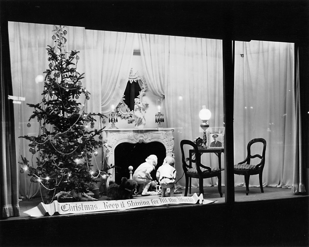 This view shows a tree and fireplace scene with children looking up the chimney. A banner proclaims 'Christmas: Keep it Shining For All the World.' c.1940. [PHOTO: Rochester Public Library]