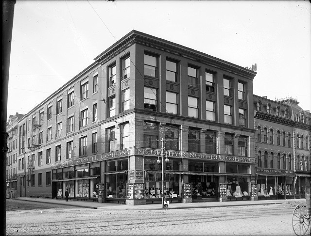 The McCurdy & Norwell Company department store was located at 285-291 Main Street East, at the corner of Elm Street. The display windows are crowded with goods. The store occupied several attached buildings of various heights and styles. c.1901-1913 [PHOTO: Albert R. Stone Collection]
