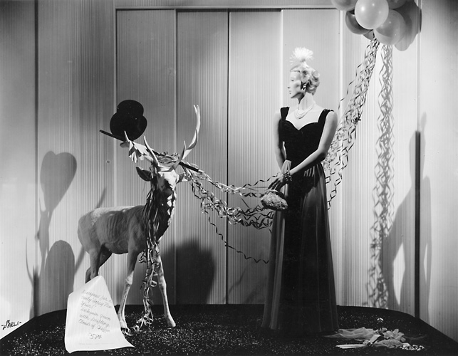 This scene shows a mannequin in an evening gown with a reindeer. c.1940. [PHOTO: Rochester Public Library]
