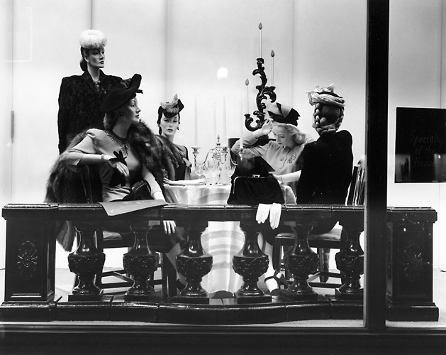 This scene shows a group of female mannequins dressed in fashionable clothes. They are seated at a table. c.1940. [PHOTO: Rochester Public Library]
