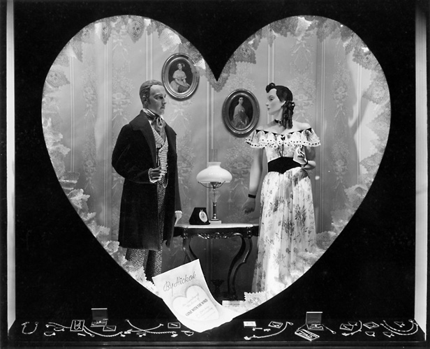 This scene was set up for Valentine's Day, and shows a Victorian era couple in a heart shape. A jewelry display is below them. c.1940. [PHOTO: Rochester Public Library]
