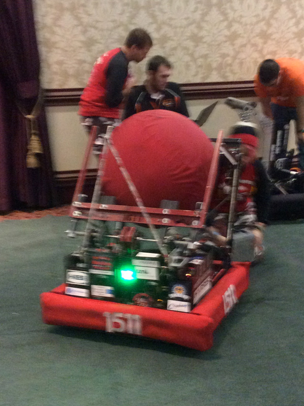 The robot has arms that hold a large fabric ball. Its arms move down and let the ball roll on the ground. The launcher then moves towards the ball and scoops it up. [PHOTO: Ella's Mom]