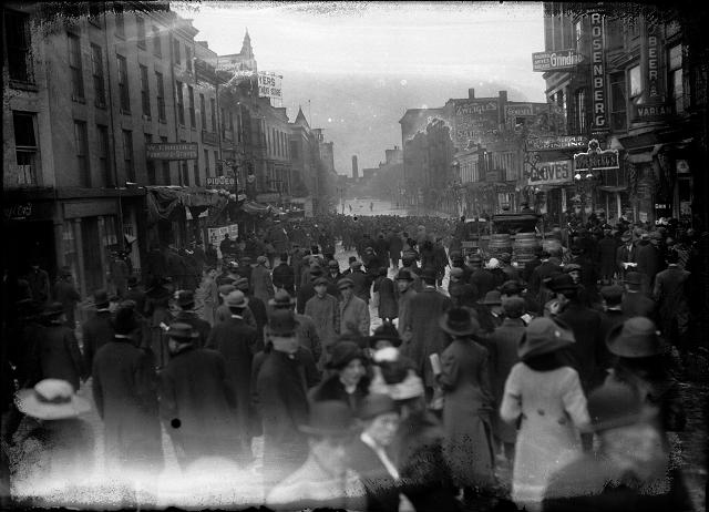 A large crowd is gathered on Front Street to look at the flood at the other end of the street. Varlan's Hotel, Rosenberg's Pawnshop, Charles Adam's Sons Grinding, J.G. Zweigle's Sons, W.T. Bridle Furniture, William Pigeon Shoes, Hyman Davis Shoes, Genesee Provision Company, Myers Department Store, and the F.H. Loeffler Company are visible in the photo. March, 1913. [IMAGE: Albert R. Stone]