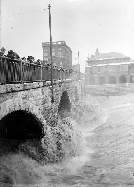 Spectators line the Court Street Bridge railings to watch flood waters beating against the arches of the bridge, below the dam. March, 1913. [IMAGE: Albert R. Stone]