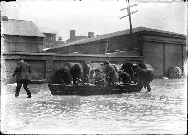 A group of men are pictured in and around a rowboat on Front Street, during the flood of 1913. March, 1913. [IMAGE: Albert R. Stone]