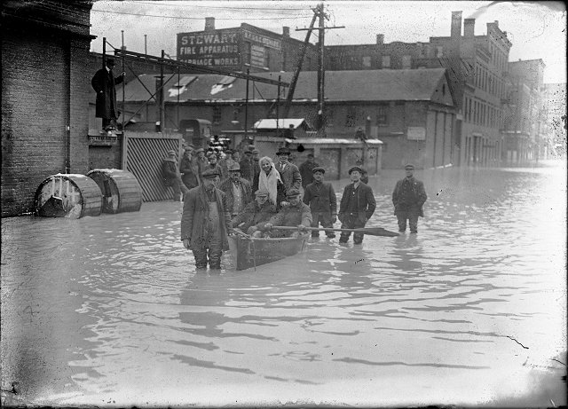 A group of people are pictured in and around a rowboat in the middle of flooded Front Street. They are members of a rescue crew that has saved a woman from a flooded building. All records for high water were broken in this flood. March, 1913. [IMAGE: Albert R. Stone]