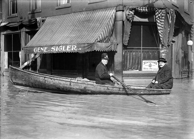 A Front Street policeman patrols his beat in a rowboat during the 1913 flood. He and another man row past the Hotel Richmond at the corner of Front and Market Streets. March, 1913. [IMAGE: Albert R. Stone]
