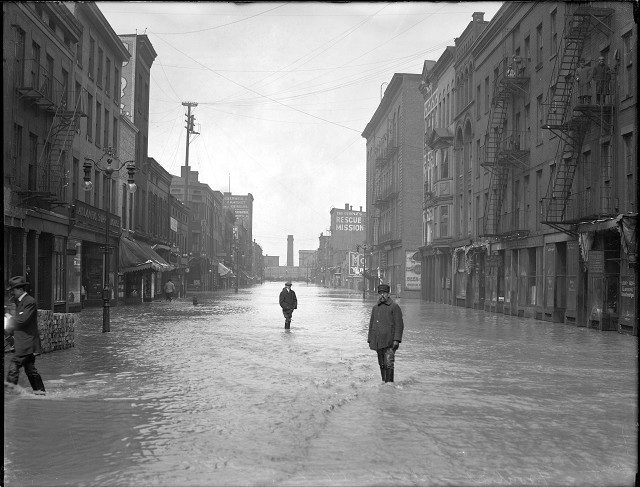 Men are standing ankle-deep in water on Front Street. On the left is the Atlantic Supply House and on the right is the People's Rescue Mission. March, 1913. [IMAGE: Albert R. Stone]