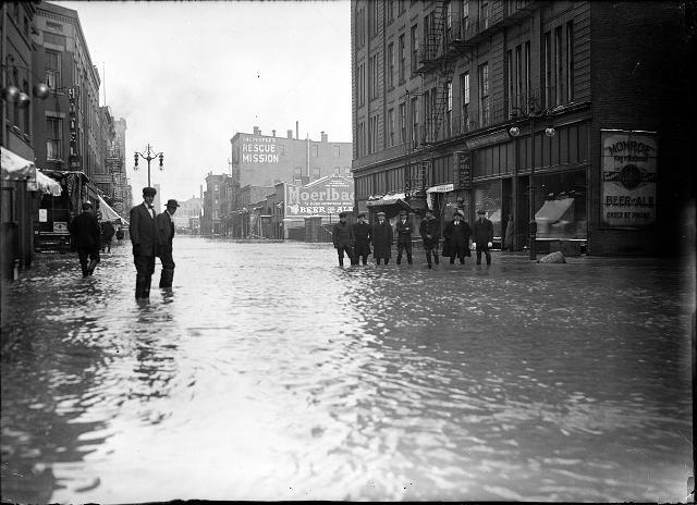 Men stand ankle deep in flood water on Front Street. They are in front of the Rochester Poultry & Commission Company. The People's Rescue Mission is in the background. March, 1913. [IMAGE: Albert R. Stone]