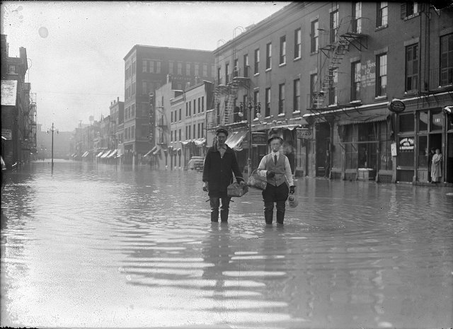 Two men stand ankle-deep in water on Front Street during the flood of 1913. They are carrying a coffee pot and baskets. On the right side of the photograph a man and a woman look out of a doorway. March, 1913. [IMAGE: Albert R. Stone]