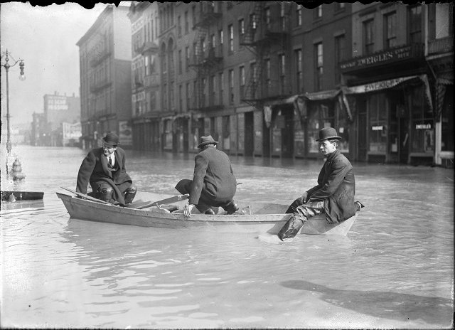 Three men ride a rowboat down flooded Front Street. They are passing J.G. Zweigle's. March, 1913. [IMAGE: Albert R. Stone]